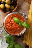 Glass jar with homemade tomato pasta sauce. Glass jar with homemade classic spicy tomato pasta or pizza sauce with olives and basil. Italian helthy food Royalty Free Stock Image