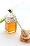 Glass jar of honey and stick Royalty Free Stock Image
