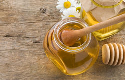 Glass jar of honey and stick on wood Stock Photo