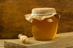 Glass jar honey withdrizzler on wooden background Stock Photos