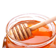 Glass jar of honey with wooden drizzler Stock Photos