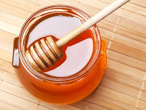 Glass jar of honey with wooden drizzler Stock Photography