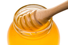Glass jar of honey with wooden drizzler isolated on white backgr Royalty Free Stock Photos