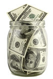 Glass jar with hundred-dollar notes. On a white background royalty free stock image