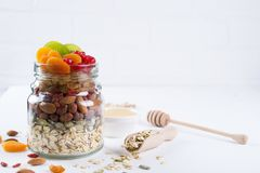 Glass jar with ingredients for cooking granola on white background. Oat flakes, honey, nuts, dried fruit and seeds. Healthy snak Royalty Free Stock Photography