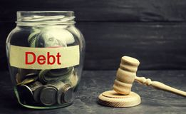 A glass jar and the inscription `debt ` and a wooden gavel. Payment of taxes and of debt to the state. Concept of financial crisis. A glass jar and the royalty free stock photo