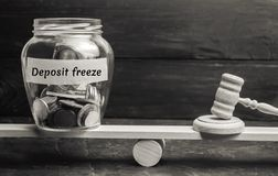Glass jar and the inscription Deposit freeze and the hammer of the judge. Assignment of money by the bank or the state. Failure to. Pay interest and dividends royalty free stock photo