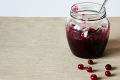 Glass jar with jam and cranberries on the table royalty free stock photography