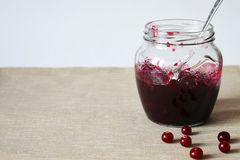 Glass jar with jam and cranberries on the table royalty free stock photo