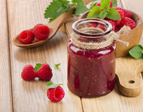 Glass jar of jam with fresh raspberries Stock Images