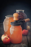 Glass jar of juice, apples and can lid closing machine for canning. Royalty Free Stock Photo