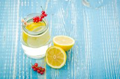 glass jar of lemonade with a lemon and red berries on a blue background/glass jar of lemonade with a lemon and red berries on a b royalty free stock image