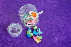 Glass Jar with Lid Off. Toppled over glass jar with handmade wooden hearts decorations and ribbon full of colorful folded paper slips royalty free stock photos