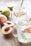 Glass jar of lime water with slices of peach royalty free stock image