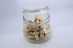 Glass jar with lots of peanuts on a white background Royalty Free Stock Images