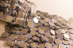 Glass jar with many mexican pesos. Coins Stock Photos