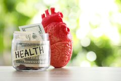Glass jar with money and heart model on table against blurred background. Space for text royalty free stock photo
