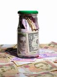Glass jar with money. Hryvnia and dollars Stock Photography