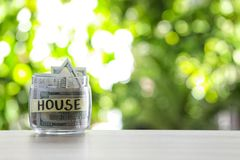 Glass jar with money and label HOUSE on table against blurred background. Space for text stock image