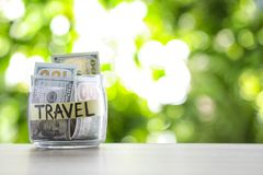 Glass jar with money and label TRAVEL on table against blurred background. Space for text royalty free stock photos