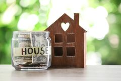 Glass jar with money for mortgage and house model on table. Against blurred background stock photo