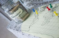 A glass jar with money put aside for a holiday with the inscription `adventure` Royalty Free Stock Image
