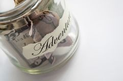 A glass jar with money put aside for a holiday with the inscription `adventure` Stock Images