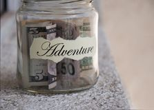 A glass jar with money put aside for a holiday with the inscription `adventure` Stock Photo