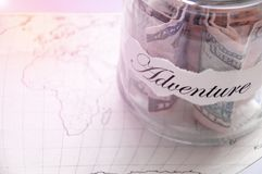 A glass jar with money put aside for a holiday with the inscription `adventure` Royalty Free Stock Photo