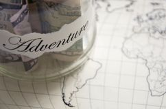 A glass jar with money put aside for a holiday with the inscription `adventure`. Royalty Free Stock Images