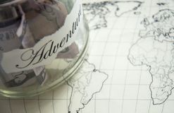 A glass jar with money put aside for a holiday with the inscription `adventure`. Stock Image