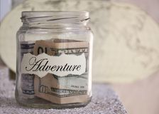 A glass jar with money put aside for a holiday with the inscription `adventure` Royalty Free Stock Photos