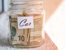 A glass jar with money put aside for a holiday with the inscription `car`. Royalty Free Stock Images