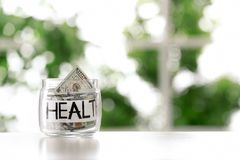 Glass jar with money and word HEALTH on table against blurred background. Space for text stock photos