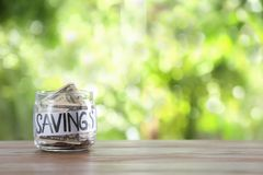 Glass jar with money and word SAVINGS on table against blurred background. Space for text stock images