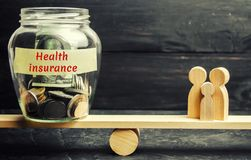 Glass jar with money and the words `Health Insurance` and the family on the scales. The concept of medical insurance of life, fami. Ly. Healthcare. The royalty free stock image