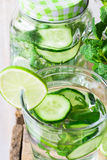 Glass and jar mug with infused detox cucumber water with lime and fresh mint, close up, cleansing Stock Images