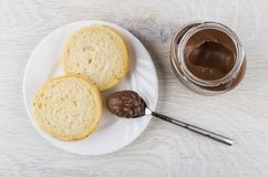 Glass jar with nut-chocolate paste, pieces of bread, teaspoon. With paste on wooden table. Top view Royalty Free Stock Image
