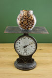 Glass jar of nuts on scale Royalty Free Stock Images