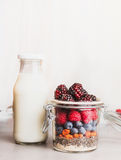 Glass jar with oatmeal , Chia seeds, Goji berries, fresh berries and bottle of milk on white wooden background, front view. Royalty Free Stock Photo