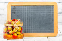 Glass jar with olives and peppers with blackboard Stock Photo