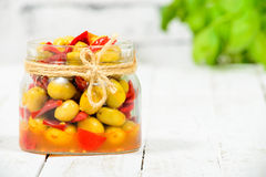 Glass jar with olives and peppers on white table Royalty Free Stock Images