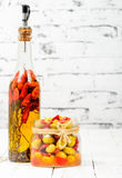 Glass jar with olives and peppers on white table Royalty Free Stock Image
