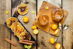 Homemade orange jam. Glass jar of orange jam with spices and firtree on wood table. Top view royalty free stock images