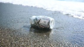A glass jar with paper money dollars against a sea waves background. Accumulate the savings on leave by the sea or the. Ocean. beach stock video footage