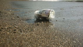 A glass jar with paper money dollars against a sea waves background. Accumulate the savings on leave by the sea or the. Ocean. beach stock video