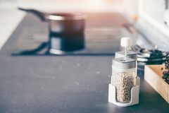 Glass jar with pepper seeds as a flavoring in modern kitchens, blurred background of Electric stove stock image
