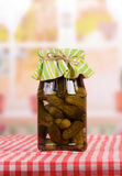 Glass jar with pickled cucumbers on background of kitchen. Stock Image