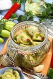 Glass jar with pickled green tomatoes prepared for winter Stock Image
