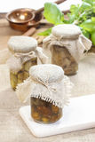 Glass jar of pickled mushrooms on jute table cloth Stock Image